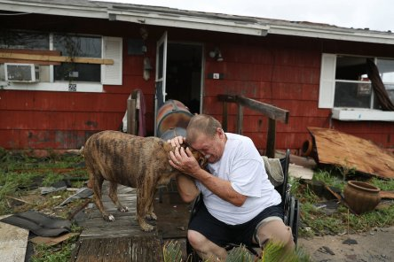 """ROCKPORT, TX - AUGUST 26: Steve Culver cries with his dog Otis as he talks about what he said was the, """"most terrifying event in his life,"""" when Hurricane Harvey blew in and destroyed most of his home while he and his wife took shelter there on August 26, 2017 in Rockport, Texas. Harvey made landfall shortly after 11 p.m. Friday, just north of Port Aransas as a Category 4 storm and is being reported as the strongest hurricane to hit the United States since Wilma in 2005. Forecasts call for as much as 30 inches of rain to fall in the next few days (Photo by Joe Raedle/Getty Images)"""